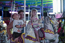 Photo of Children and Mother on a Carousel